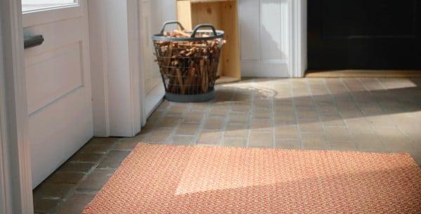 Shelbourne Orange/Yellow Eco Cotton Rug on a brick floor